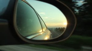 stock-footage-early-morning-drive-on-a-country-road-with-view-of-sunrise-from-side-mirror-of-the-car